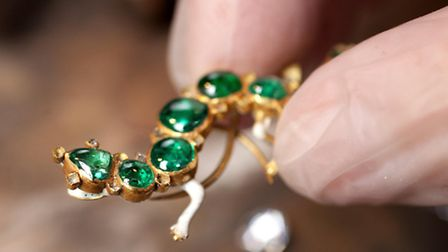 Examining Salamander brooch set in gold with emeralds and diamonds [Picture: David Parry]