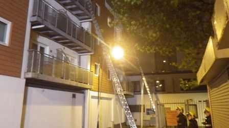 Firefighters use ladders to rescue trapped residents at a block of flats in Commercial Road, Stepney