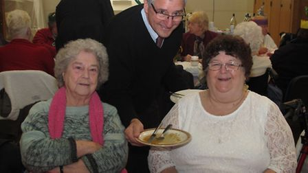 MP Jim Fitzpatrick collects the dishes while volunteering at Neighbours In Poplar's luncheon club