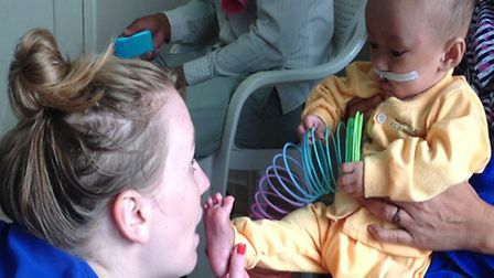 Rebecca Knill helping an infant in Cambodia