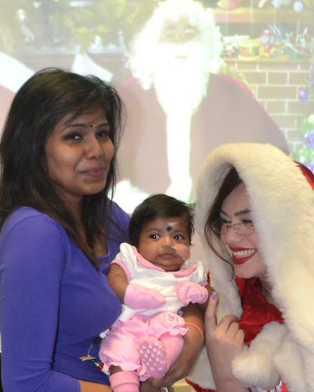 Babintha Mathan and baby daughter with Mary Claus and the Santa video link behind them
