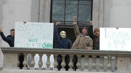 Defiant... squatters at the Royal Mint give a hand-fist wave from balcony [photo: Ken Mears]