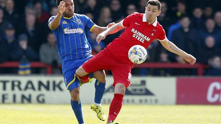 Leyton Orient midfielder Lloyd James looks to move the ball forward with AFC Wimbledon's Andy Barcha