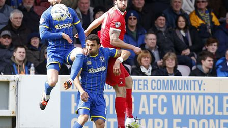 Leyton Orient forward Ollie Palmer challenges for the ball with two AFC Wimbledon opponents (pic: Si