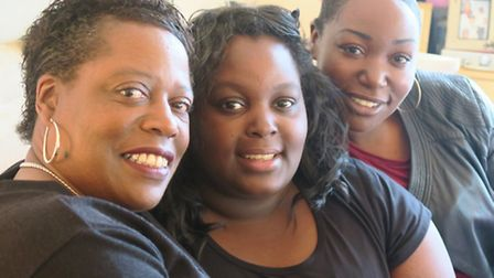 Ebony Caesar (centre) resting at home in Poplar with mum June (left) and sister Joy