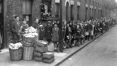 1913... Clara Grant's famous 'Farthing Bundle' queue at Fern Street Settlement in Bromley-by-Bow