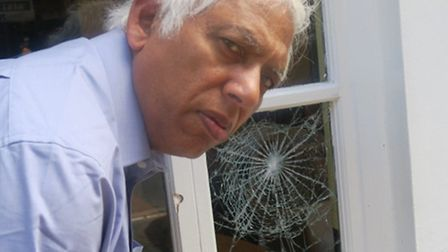 Brick Lane curry house owner Azmal Hussain examines the damage
