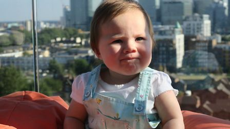 Baby-in-the-sky... even the 12th floor isn't enough to keep little Caron Grisalesova, 10 months, fre