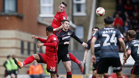 Leyton Orient defender Aron Pollock gets up well to beat Doncaster Rovers Tommy Rowe to the ball (pi