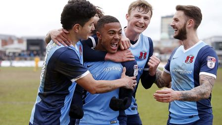 Josh Koroma (centre) is mobbed by his Leyton Orient team-mates after completing his hat-trick at New
