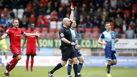 Referee Charles Breakspear shows the red card to Leyton Orient defender Tom Parkes (out of picture)