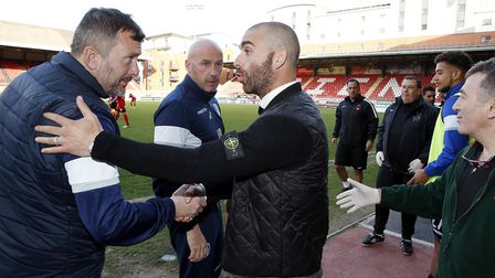 Leyton Orient boss Omer Riza shakes hands with the Colchester United staff after Saturday's game fin