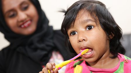 Little Maidah at 22 months learns to brush her own teeth, watched by her mum Shabana Begum. Picture: