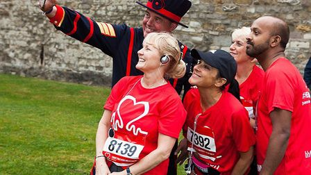 Beefeater shows runners The Tower sites after their exhausting fun run in the moat. Picture: BRAD IN