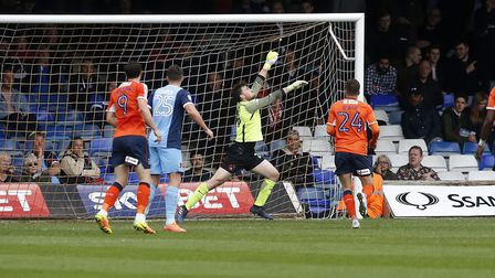 Leyton Orient goalkeeper Sam Sargeant pushes a volley from Luton Town's Luke Gambin over the crossba