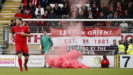 A flare is thrown onto the pitch near Leyton Orient goalkeeper Sam Sargeant and a pitch protest quic