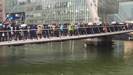 Commuters packed onto South Quay footbridge to get to Canary Wharf station. Picture: Sergey Kharlamo