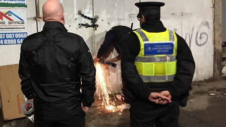 Bailiffs and council enforcement officers busting into illegal peanut-roasting shack under Fenchurch