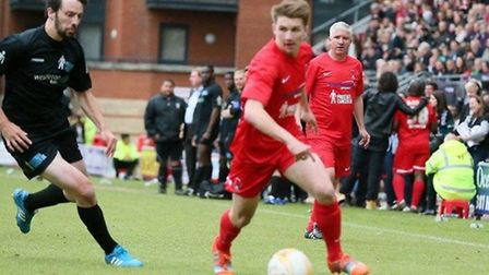 Martin Ling watches on as his son Sam Ling tries to go past Men United's Ralph Little at a charity m