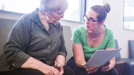 A patient in her 70s gets help filling out medical paperwork at her GP surgery for a routine healthc
