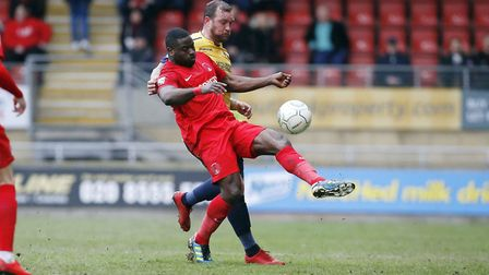 Leyton Orient centre back George Elokobi clears the ball forward despite close attention from Ebbsfl