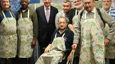 The Men's Cabin OAP group and MP Jim Fitzpatrick with their apron designs. Picture source: Poplar Ha
