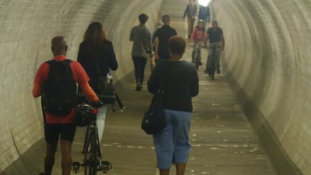 Two cyclists clearly seen riding through the foot tunnel under the Thames while a third correctly wa