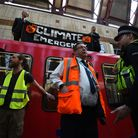 Climate activists have climbed on top of a Dockland Light Railway at Canary Wharf station as part o