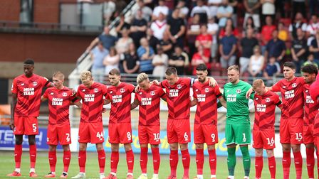 Leyton Orient players stand for a minute's silence in memory of former manager Justin Edinburgh duri
