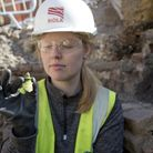 An archaeologist holding part of a money pot found on site at the Boar's Head. Picture: MOLA