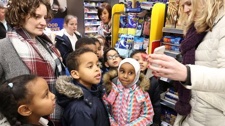 Pupils from Cubitt Town Priimary check the sugar content using an app at Nisa foodstore with Cllr Am