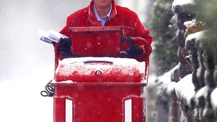 A Royal Mail employee delivers mail in the heavy snow. Photo credit should read: Peter Byrne/PA Wire