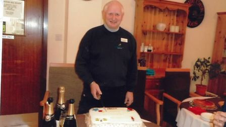 Michael Green poses with cake and champagne at his retirement party