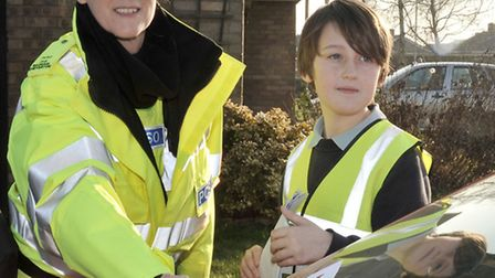 Children at Cavalry Primary School hand out parking posters with a PCSO Rachael Cheverton.
