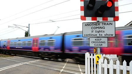 A First Capital Connect train passes through the Queen Adelaide level crossing heading to King's Lyn