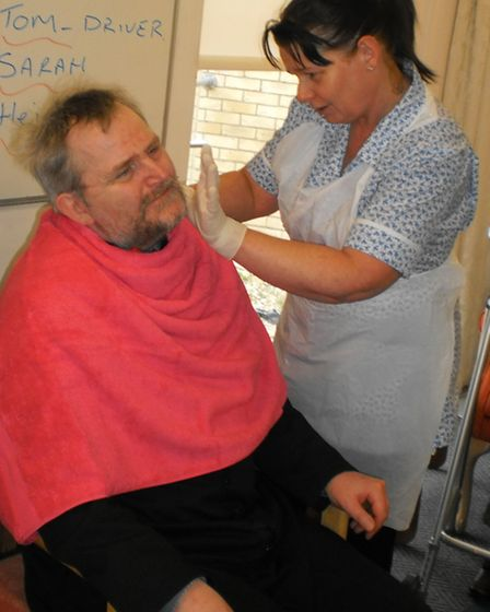Sarah Stacey, a member of the care team at Edina Court, shaves off Franz Reinbolds beard