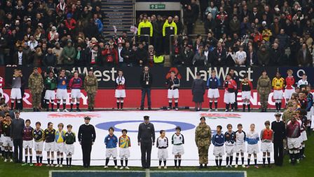 100 schoolchildren wear colourful rugby shirts as they flank the military before kick off at the RBS