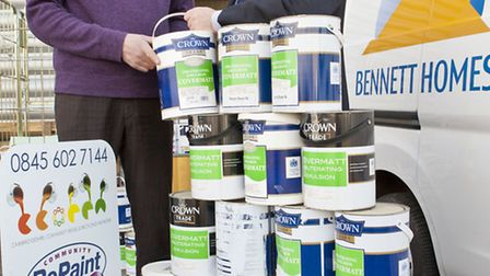 Colin Sells, Bennett Homes construction manager (right) hands over the paint to Marcus Pheasant, dev