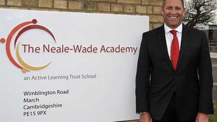 Neale Wade Academy March. Principal Jason Wing next to the new sign and logo.