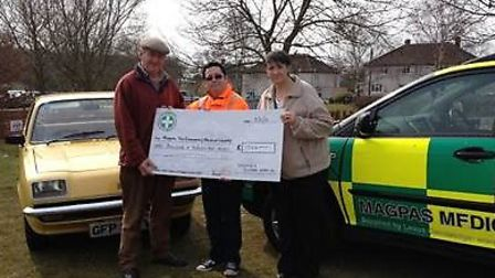 Organisers Trevor and Linda Brown present Ivor Sanderson, Magpas collections assistant, with £1,024.