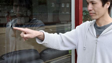 Chang Hun Ho from the Ruby Chinese on Nene Quay Wisbech. pointing at the hole in shop window.