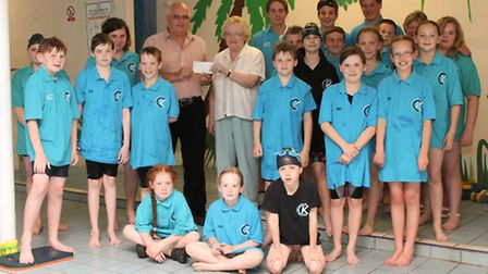 Cllr John Chambers presenting the cheque to Joan Fresher, surrounded by members and swimmers