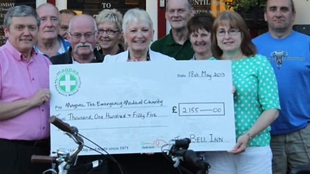 Andy Kedziora, his wife Dawn (far right) and volunteers hand over the cheque to Magpas representativ