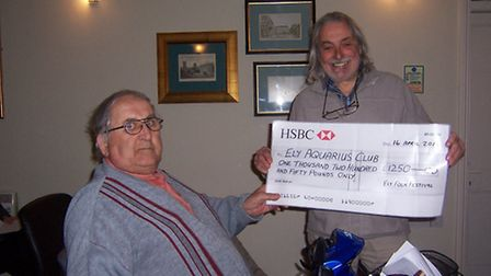 Andy Wall, chairmam of Ely Folk Festival committee presenting a cheque to George Reed, treasurer of
