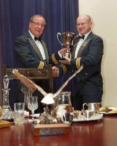 Wing Commander Bower receives a trophy in acknowledgement of his long standing service.