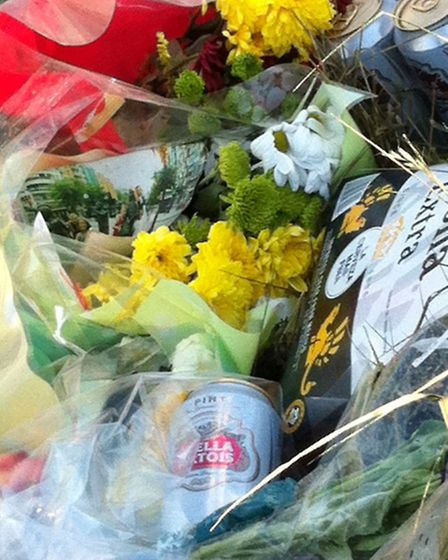 Bottles of beer, cards and dozens of flowers were left in tribute