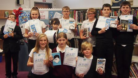 Students with their certificates and copies of the book they had to read.