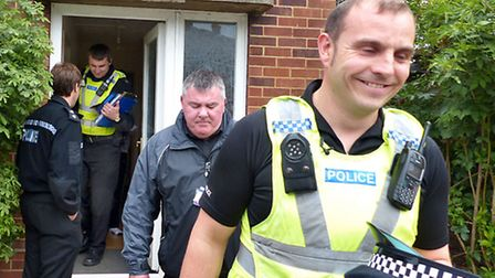 Pc Nick Webber, Bill Tilley of Fenland District Council and PCSO Aivaras Krochalev leaving the house