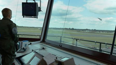 Max Rowlandson watches an F-15 fighter jet fly from the aircraft control tower.