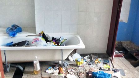 Empty cider bottles and rubbish scattered on the floor and in the bath at the squat in Norwich Road,